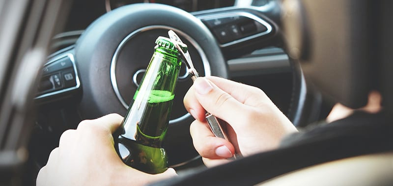 Driver opening beer from the drivers seat of a car