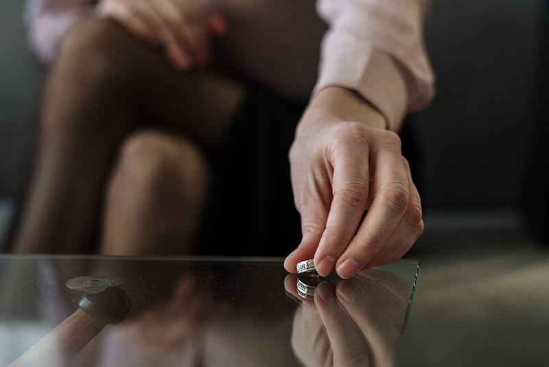 Woman placing wedding ring on tabletop